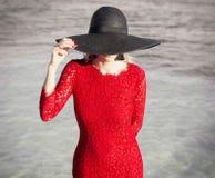 Mulher no vestido e no chapéu negro vermelhos Fotografia de Stock Royalty Free
