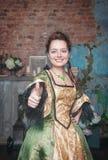 A mulher no vestido medieval que mostra os polegares levanta o sinal Fotografia de Stock