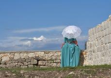 Mulher no vestido medieval que olha longe da parede do castelo Imagem de Stock