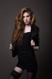 Mulher no vestido, no casaco de cabedal e em meias pretos Fotografia de Stock Royalty Free
