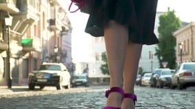 A mulher no vestido preto e em sapatas roxas nos saltos altos está andando no movimento lento filme