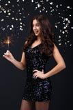 Mulher no vestido preto que guarda o chuveirinho Fotos de Stock Royalty Free