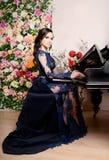 Mulher no vestido profundamente azul do laço que joga o piano e as flores Ilustração retro do vintage style fotos de stock