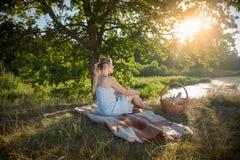 Mulher no vestido que relaxa na cobertura sob a árvore e que olha o sol Fotografia de Stock Royalty Free
