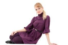 Mulher no vestido que senta-se em um branco Foto de Stock