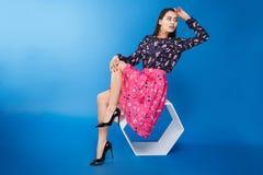 Mulher no vestido que senta-se na cadeira moderna fotos de stock royalty free