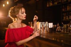 A mulher no vestido vermelho bebe o cocktail no contador da barra fotografia de stock royalty free