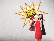 A mulher no vestido vermelho com dois sacos de compras aproxima o cartaz grande da venda Foto de Stock