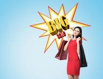 A mulher no vestido vermelho com dois sacos de compras aproxima o cartaz grande o da venda Foto de Stock Royalty Free