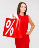 Mulher no vestido vermelho com sacos de compras Fotografia de Stock