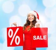 Mulher no vestido vermelho com sacos de compras Imagem de Stock