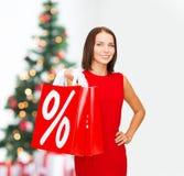 Mulher no vestido vermelho com sacos de compras Fotos de Stock