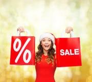 Mulher no vestido vermelho com sacos de compras Fotografia de Stock Royalty Free