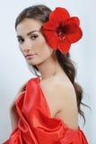 Mulher no vestido vermelho com um lírio vermelho em seu cabelo foto de stock