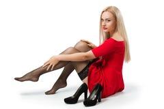 A mulher no vestido vermelho decola suas sapatas foto de stock royalty free