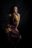 Mulher no vestido vermelho-dourado no fundo preto Imagens de Stock Royalty Free