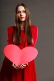 A mulher no vestido vermelho guarda o sinal do coração Foto de Stock
