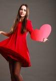A mulher no vestido vermelho guarda o sinal do coração Fotos de Stock