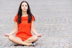 A mulher no vestido vermelho meditates Imagens de Stock Royalty Free