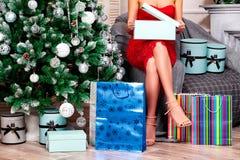 Mulher no vestido vermelho que abre suas caixas de presente do Natal Fotos de Stock