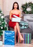 Mulher no vestido vermelho que abre suas caixas de presente do Natal Fotografia de Stock Royalty Free