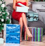 Mulher no vestido vermelho que abre suas caixas de presente do Natal Fotos de Stock Royalty Free