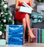 Mulher no vestido vermelho que abre suas caixas de presente do Natal Fotografia de Stock