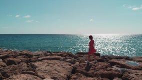 Mulher no vestido vermelho que anda na praia rochosa do cais com as ondas que batem os penhascos e o sol que brilham no dia ensol filme