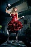 Mulher no vestido vermelho que está sobre a mesa de jantar Foto de Stock