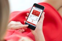 Mulher no vestido vermelho que guarda o telefone com compra em linha do app imagem de stock