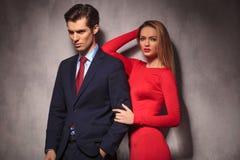 Mulher no vestido vermelho que inclina seu cotovelo no boyfriend& x27; ombro de s fotografia de stock