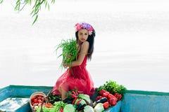 Mulher no vestido vermelho que senta-se em um barco Imagens de Stock Royalty Free