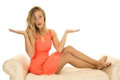 A mulher no vestido vermelho senta-se nas mãos brancas do sofá acima Foto de Stock Royalty Free