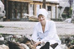 A mulher no veterinário novo de sorriso do roupão verifica as galinhas sobre Foto de Stock