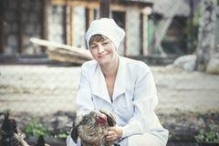 A mulher no veterinário novo de sorriso do roupão verifica as galinhas sobre Foto de Stock Royalty Free