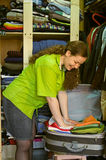 A mulher no wardrobe embala coisas em uma mala de viagem Foto de Stock