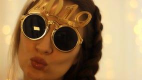 Mulher nos óculos de sol com os sorrisos do número 2019 no ano novo closeup filme