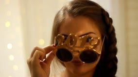 Mulher nos óculos de sol com os sorrisos do número 2019 no ano novo closeup video estoque