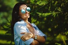 A mulher nos óculos de sol está na natureza do verão sob o sol Imagens de Stock Royalty Free