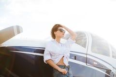 Mulher nos óculos de sol que estão fora perto do plano privado pequeno Fotografia de Stock