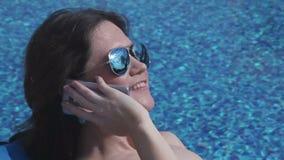 Mulher nos óculos de sol que têm a conversa telefônica, emoções positivas filme