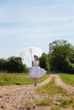 A mulher nos anos 50 de um vintage equipa o passeio em um trajeto no natur Imagem de Stock Royalty Free