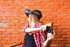 Mulher nos auriculares da realidade virtual ou nos vidros 3d e nos fones de ouvido que jogam o jogo de vídeo com gamepad do contr foto de stock royalty free