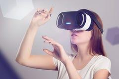 Mulher nos auriculares de VR que olham acima e que tentam tocar em objetos