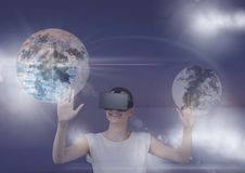 Mulher nos auriculares de VR que tocam nos planetas 3D com os alargamentos contra o fundo roxo Imagem de Stock Royalty Free