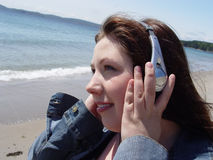 Mulher nos auscultadores na praia Fotografia de Stock Royalty Free
