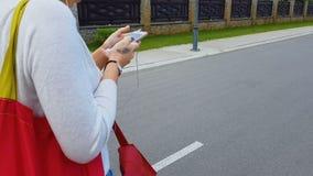 Mulher nos fones de ouvido que anda na rua da cidade que olha no smartphone, aplicação vídeos de arquivo