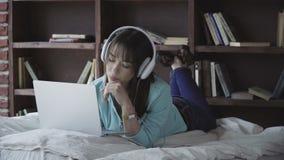 Mulher nos fones de ouvido que trabalham em um portátil video estoque