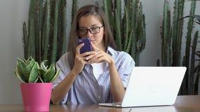 Mulher nos monóculos usando seu smartphone, portátil no portátil da tabela video estoque