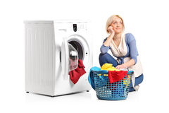 Mulher nos pensamentos assentados ao lado de uma máquina de lavar Fotografia de Stock Royalty Free